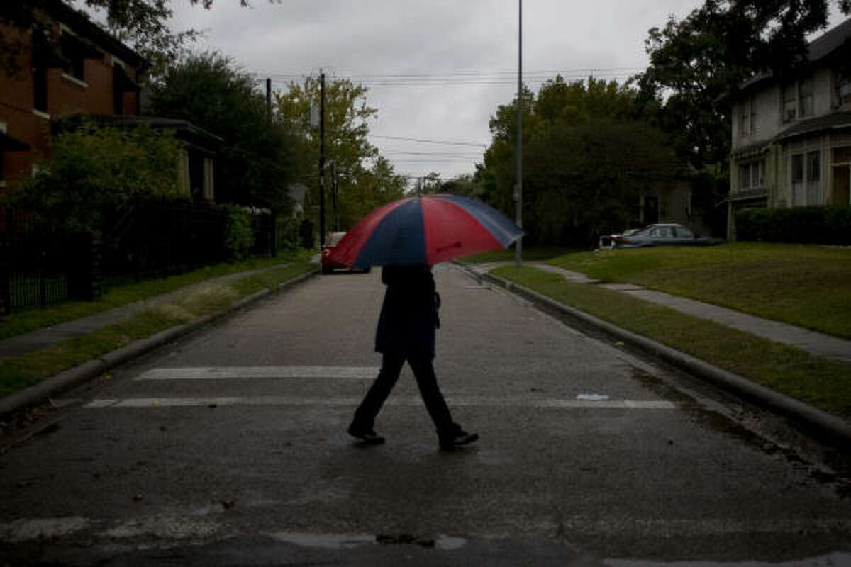 Vilma Figueroa walks along Heights Blvd. and 10 1/2 St. in the Heights neighborhood as rain fell this morning across the Houston area.
