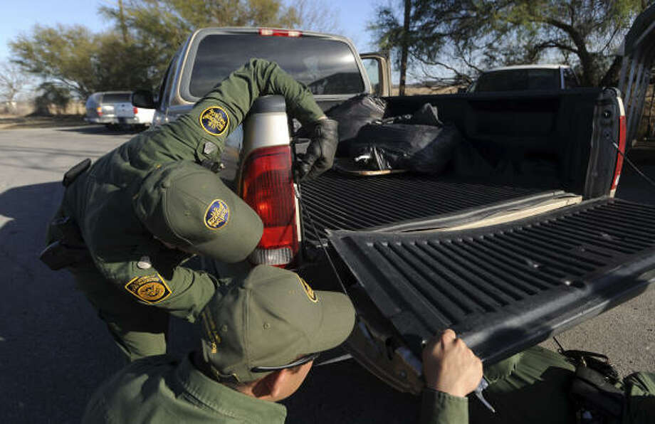Border Patrol agents examine a truck tailgate for signs of concealed drugs at the Cline checkpoint on U.S. 90 east of Del Rio. Photo: BILLY CALZADA, SAN ANTONIO EXPRESS-NEWS