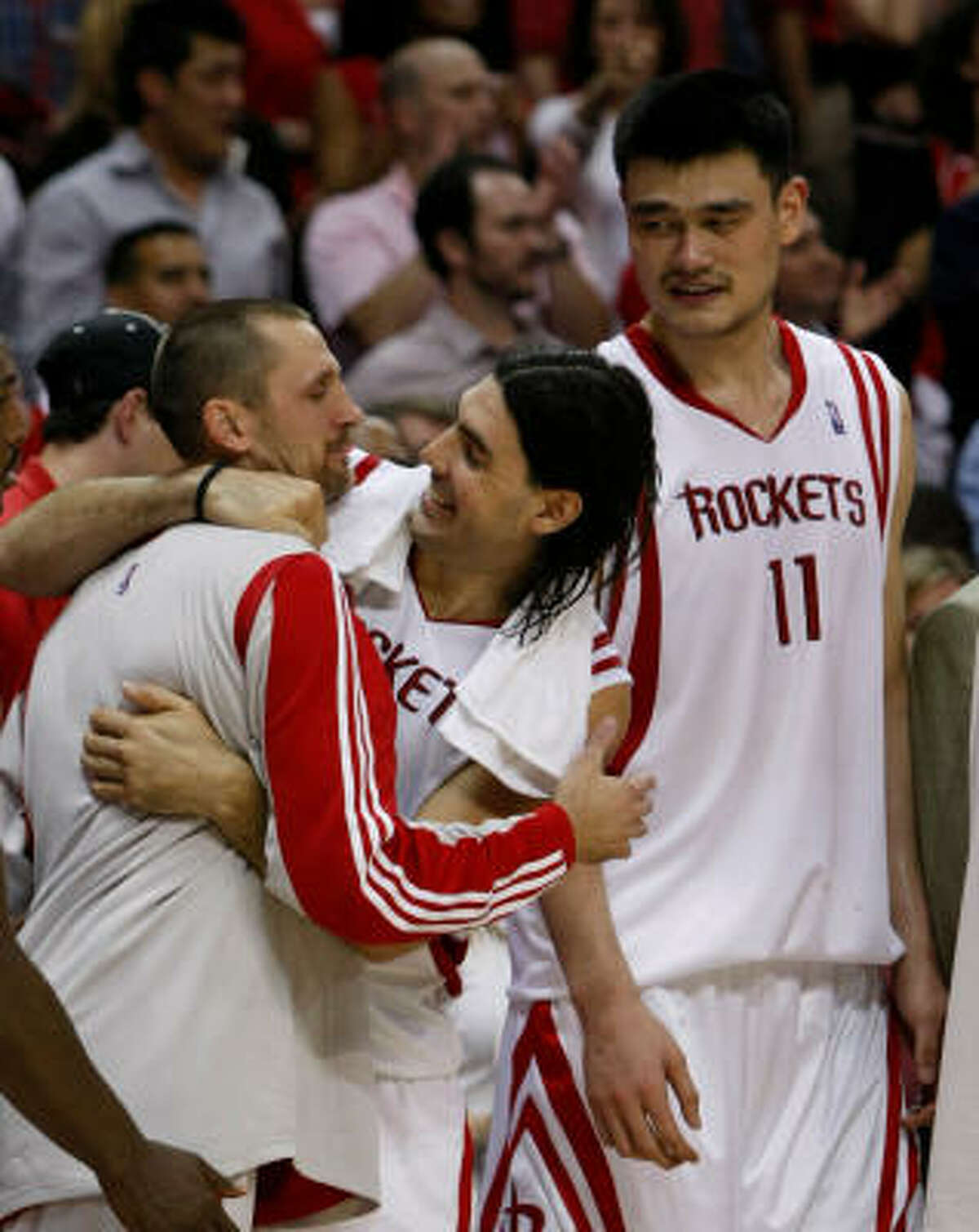 Rockets players including, from left, Brent Barry, Luis Scola and Yao Ming were ecstatic on Thursday but know more work remains.