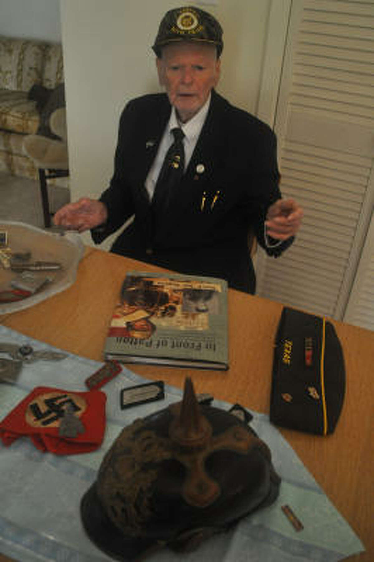 REMEMBERING THE WAR: Denis Bergeron shows some of his World War II relics and the book he wrote about his war experiences.