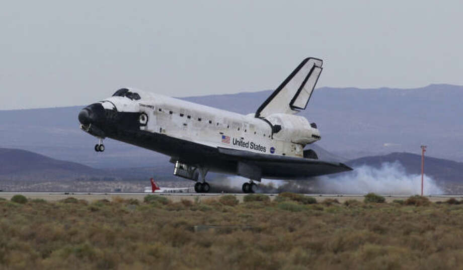 After being unable to land at Kennedy Space Center in Florida, the space shuttle Discovery touches down at Edwards Air Force Base, Calif., on Friday. Discovery astronauts were gone 14 days in a resupply mission to the space station. Photo: Reed Saxon, ASSOCIATED PRESS