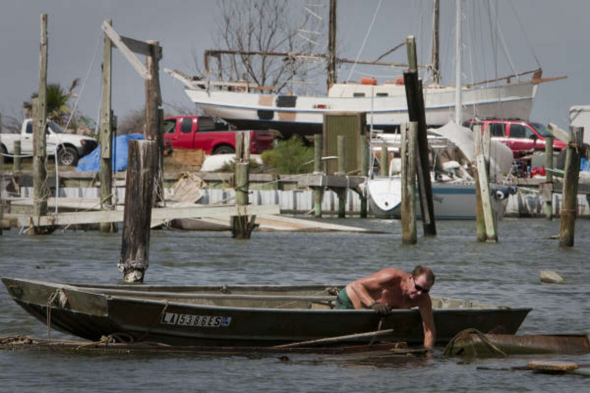 Captain Fred Morgan cleans debris left by Hurricane Ike at Galveston's Payco Marina last month. A concerted effort is slowly bringing the bay back to a semblance of normalcy.