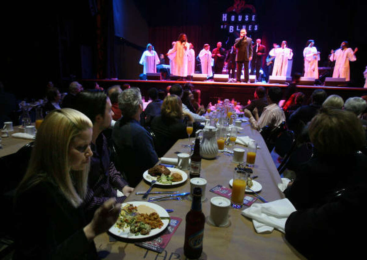 Susan Berry eats while listening to the Hensley Ensemble while they perform during The House of Blues Gospel Brunch.
