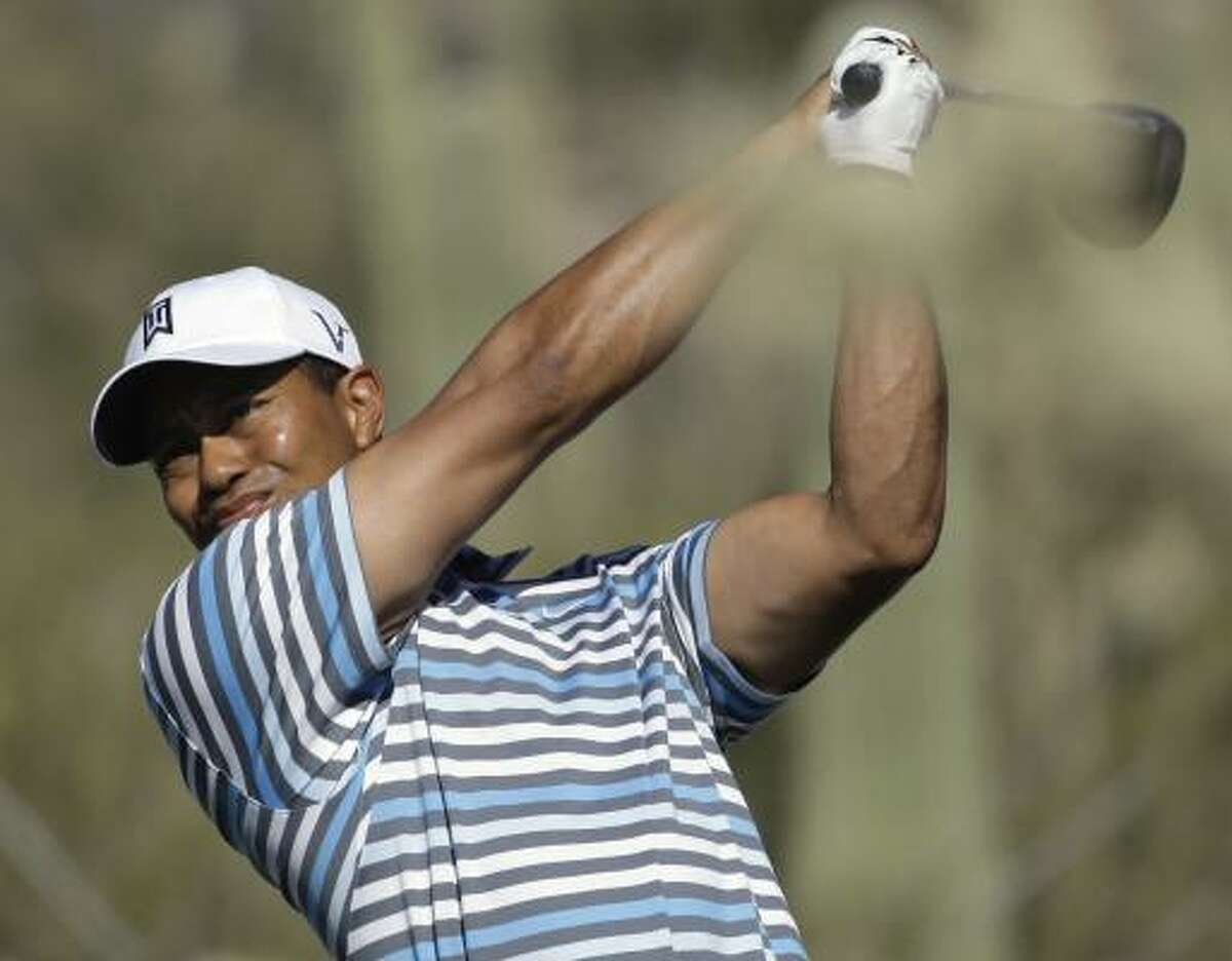 Tiger Woods blast a tee shot during a practice round at the World Golf Championships Accenture Match Play Championship on Tuesday.