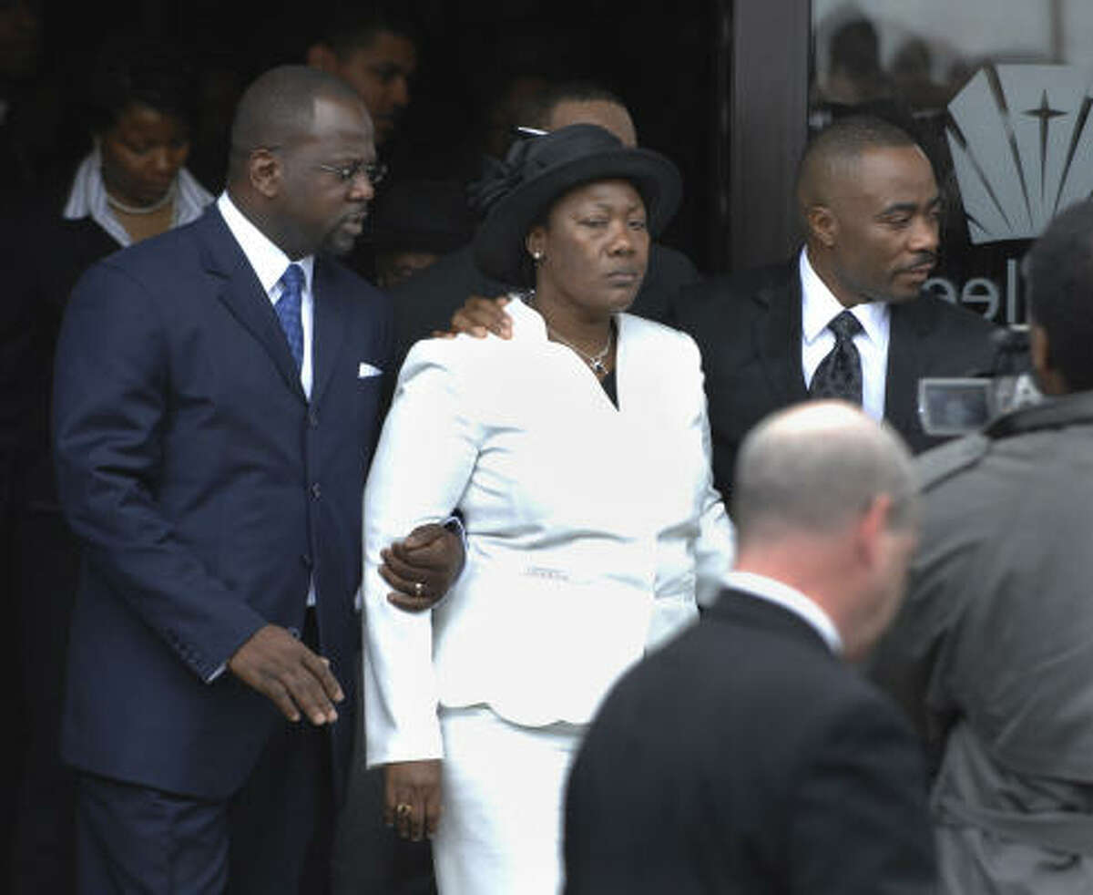 Family spokesman Ernst Guerrier, left, escorts the siblings' parents, Regine and Vronze Revelus, after the funeral for Bianca, Samantha and Kerby Revelus in Boston on Saturday.