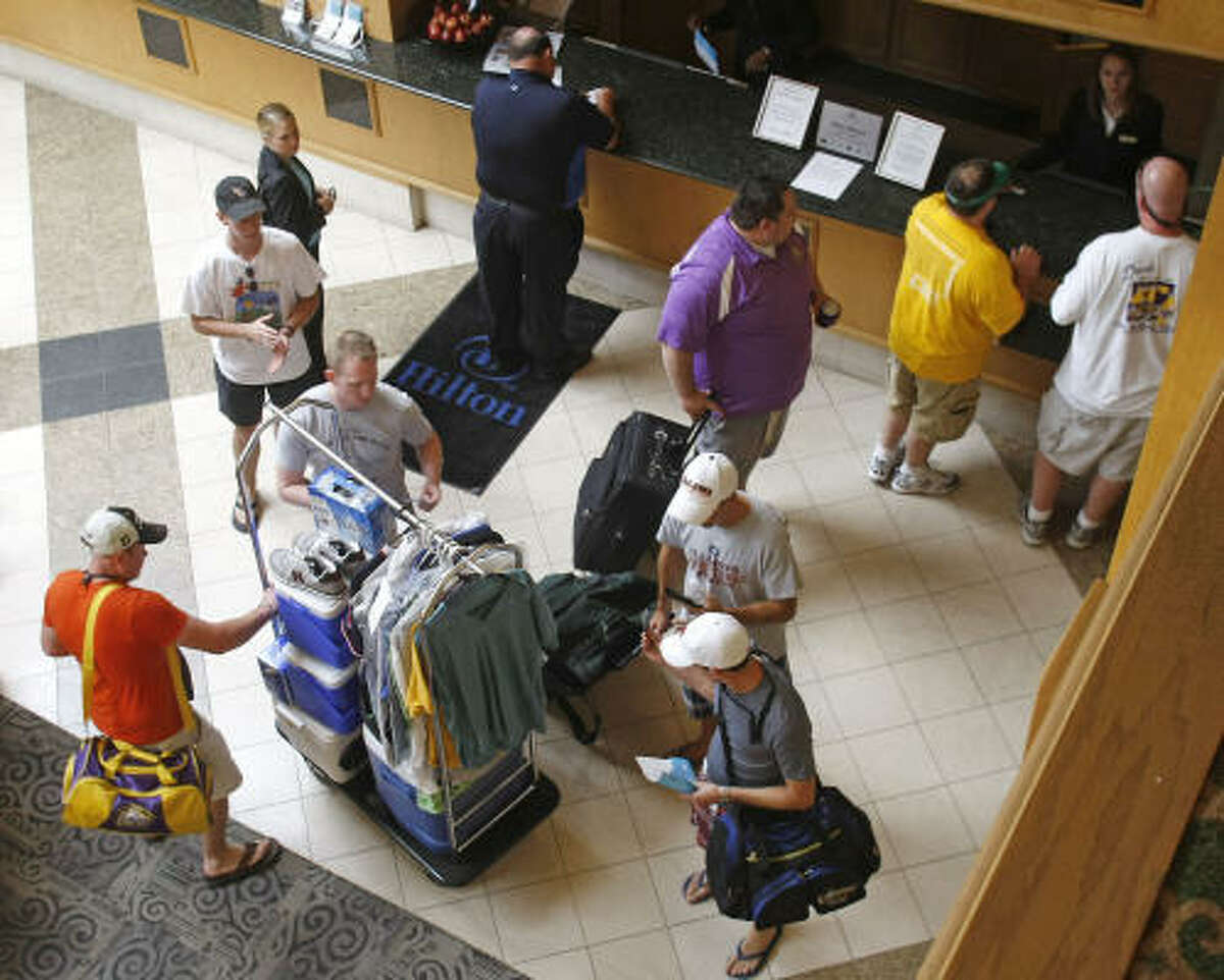 A group of baseball fans from Monroe, La., check into the Arlington Hilton for the Boston Red Sox series against the Texas Rangers on Friday.