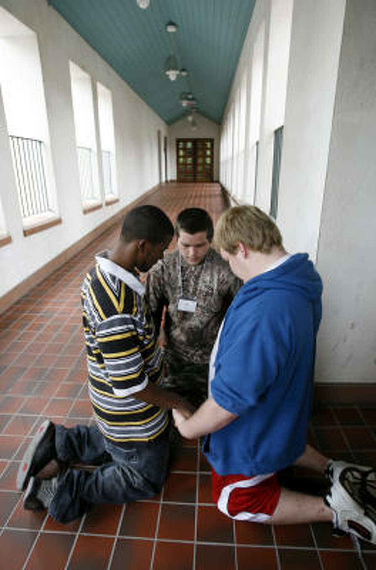 Clay Benton, 18, center, prays with his friends Terrence Payton, 18, left, and Zach Thomas, 17.