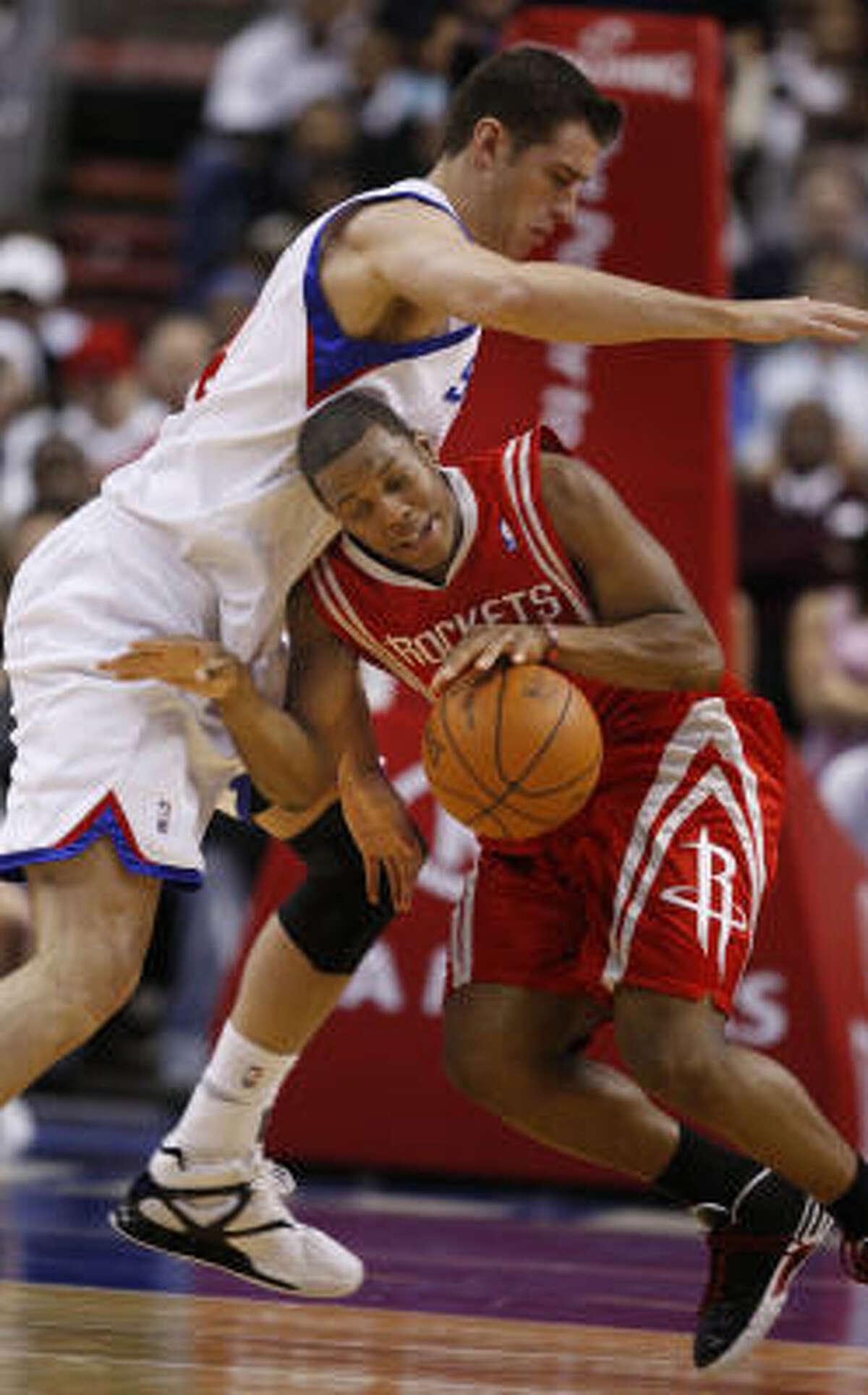 76ers center Jason Smith fouls Rockets guard Kyle Lowry.