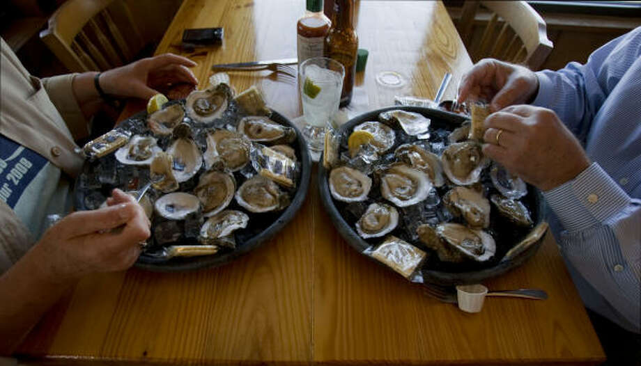 GOOD FOOD: Patrons eat oysters for lunch at Stingaree Restaurant, an iconic eatery on Crystal Beach. Photo: Sharon Steinmann, Chronicle