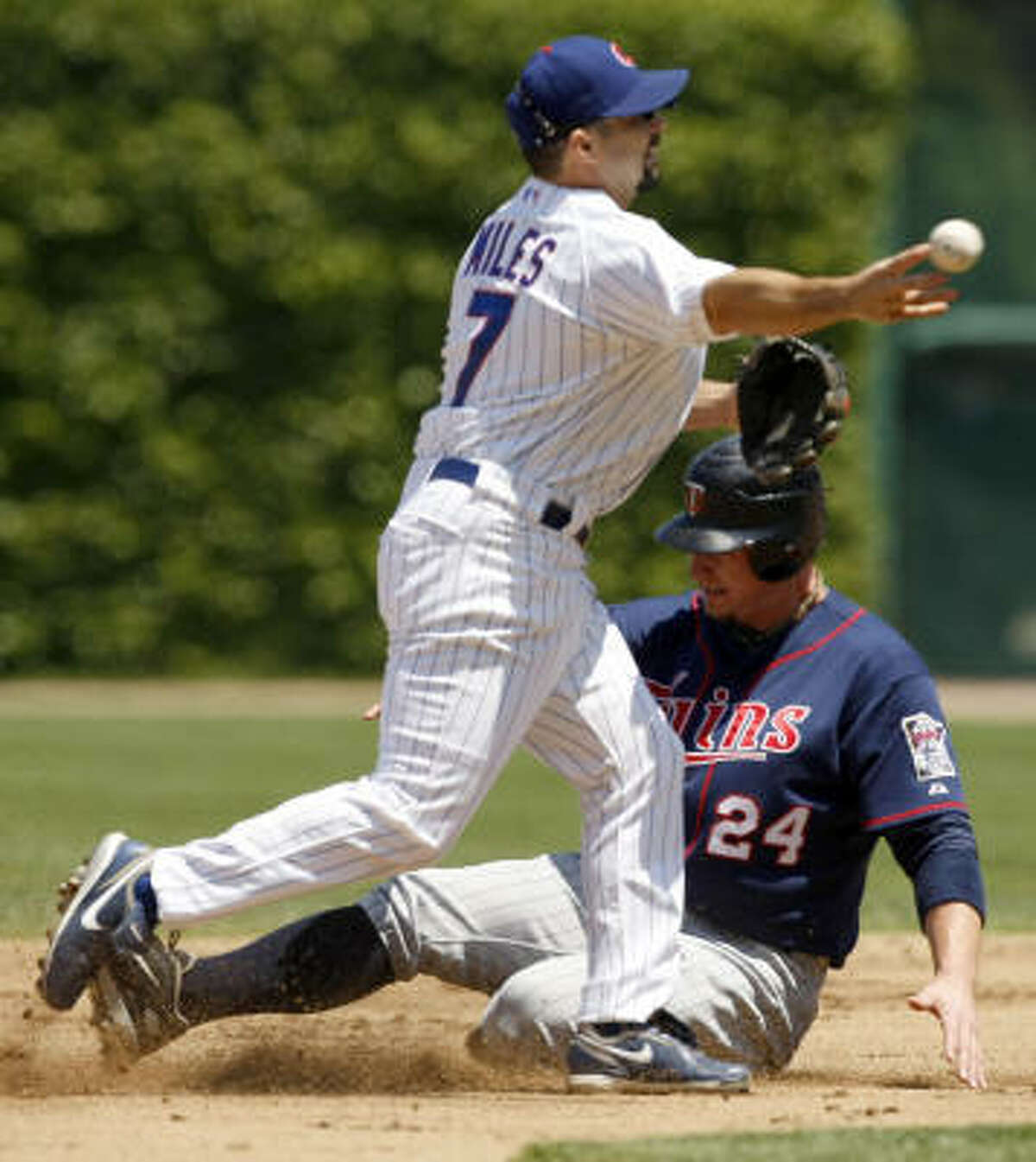 The Cubs' Aaron Miles forces out Minnesota's Joe Crede at second base in the second inning June 12, at Wrigley Field.