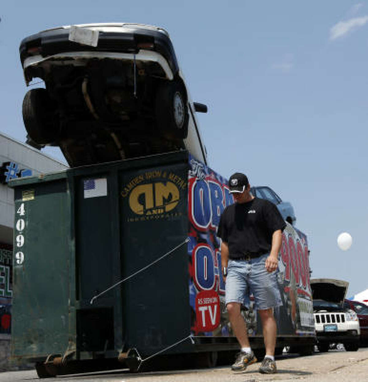 A person passes a car in a Dumpster placed in front of an auto dealership in Philadelphia as a promotion for the