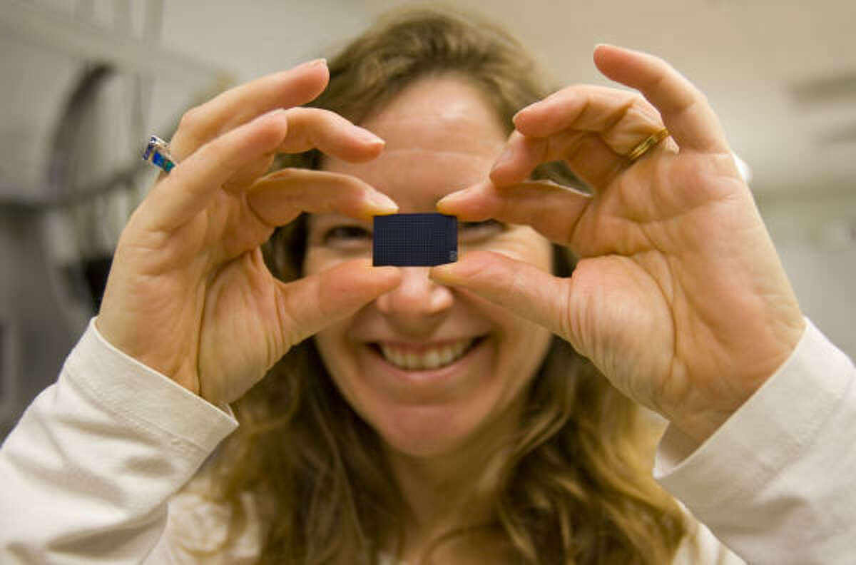 This chip, held by Katherine Stemke Hale, an instructor in systems biology at M.D. Anderson's Institute for Personalized Cancer Therapy, can activate genes in tumors.