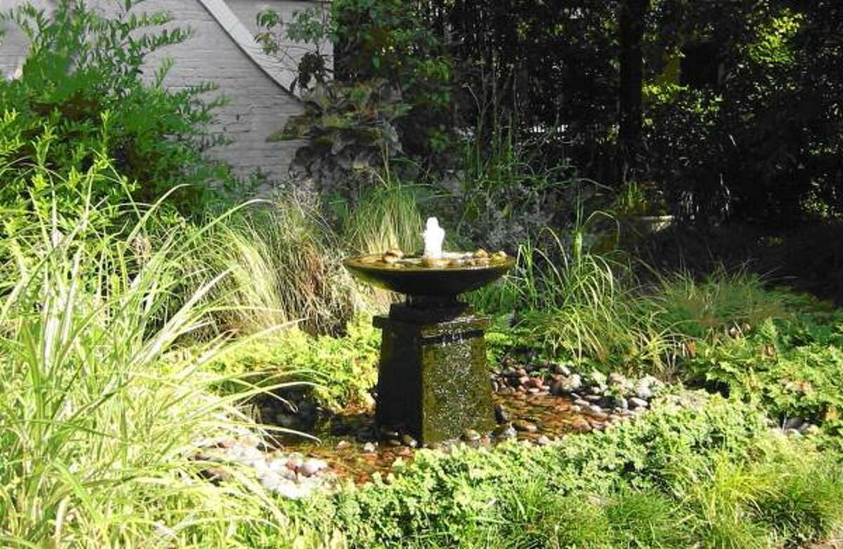 This antique garden urn and pedestal was transformed into a garden water feature by placing it in a fiberglass basin that was set at the same elevation as the surrounding planting bed. Large river cobbles disguise the fiberglass basin.