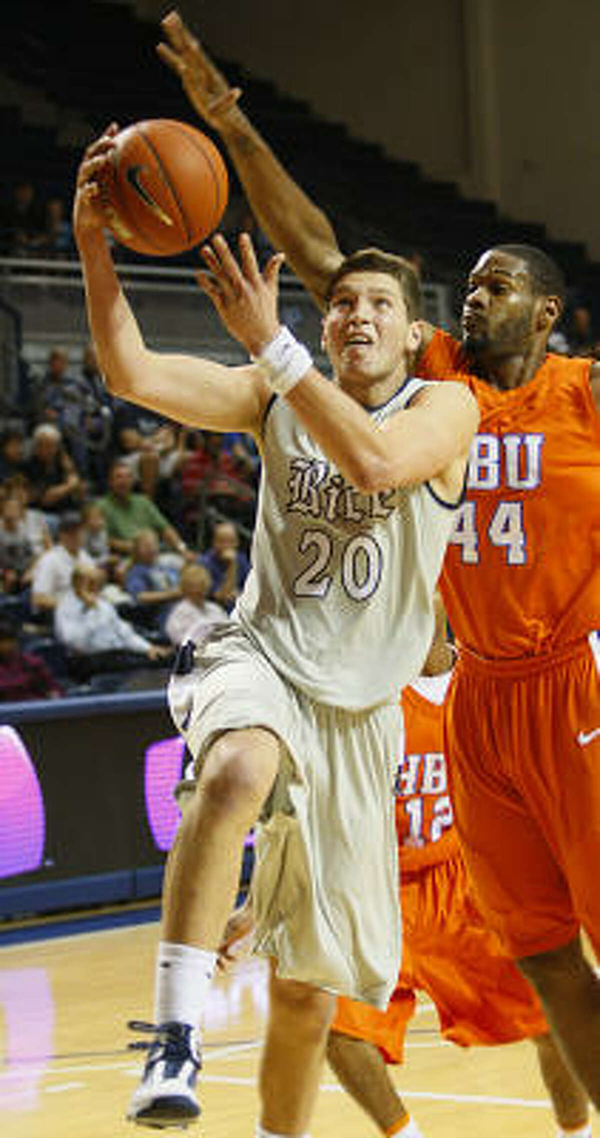 Rice's Lucas Kuipers, left, grabs a rebound in front of Houston Baptist's Damian Lewis in the Owls' win Sunday.