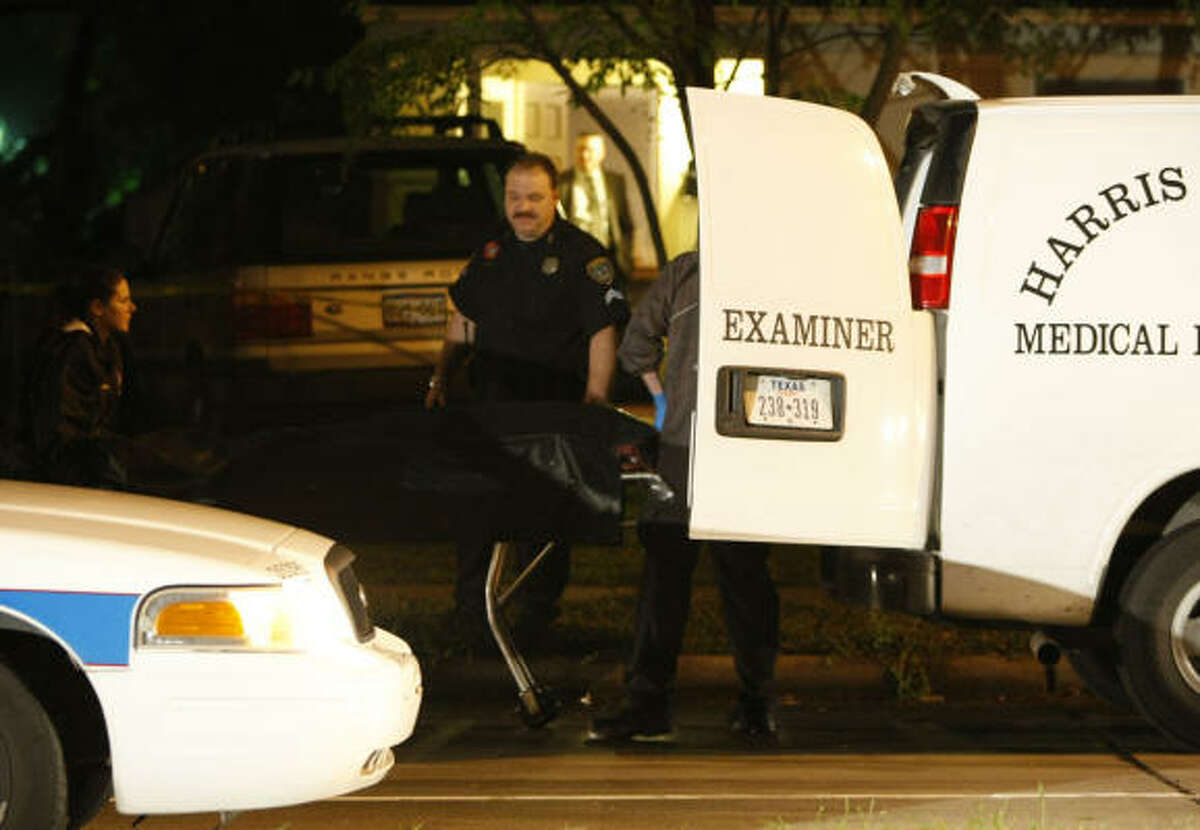 Harris County Medical Examiner officers take the body of the slain teen into a van on Sunday.