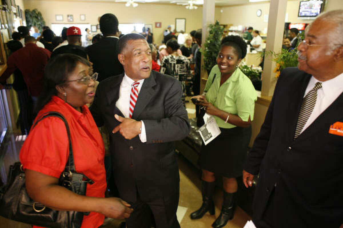 Mayoral candidate Gene Locke greets Linda Ross, left, during his visit to This Is It, a soul food restaurant, before heading out for TV and radio interviews.
