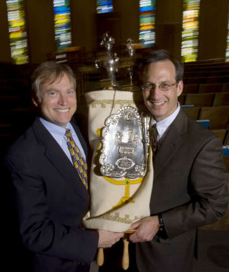 Steven Gross, left, senior rabbi of Houston Congregation for Reform Judaism, and David Lyon, senior rabbi of Congregation Beth Israel, hold a Beth Israel Torah that a member of both congregations paid to have restored and donated to HCRJ. Photo: Johnny Hanson, Chronicle