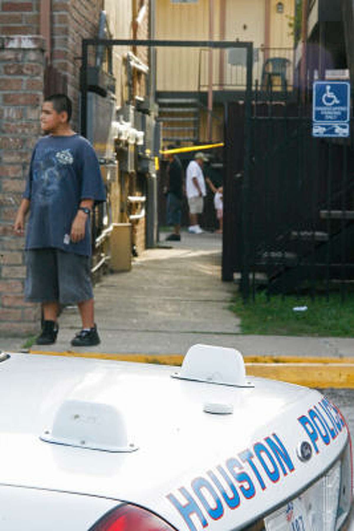 Residents of the Renwick Square Apartments wander near the scene where a HPD canine officer shot a suspect.