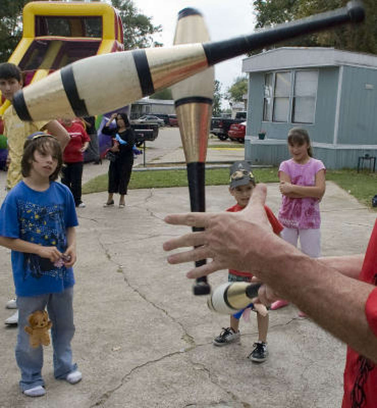 Alex Martinez, left, his brother, Ernesto, and Erika Deleon admire the dexterity of a juggler who entertained the resident owners of the Pasadena Trails mobile home park on Saturday.