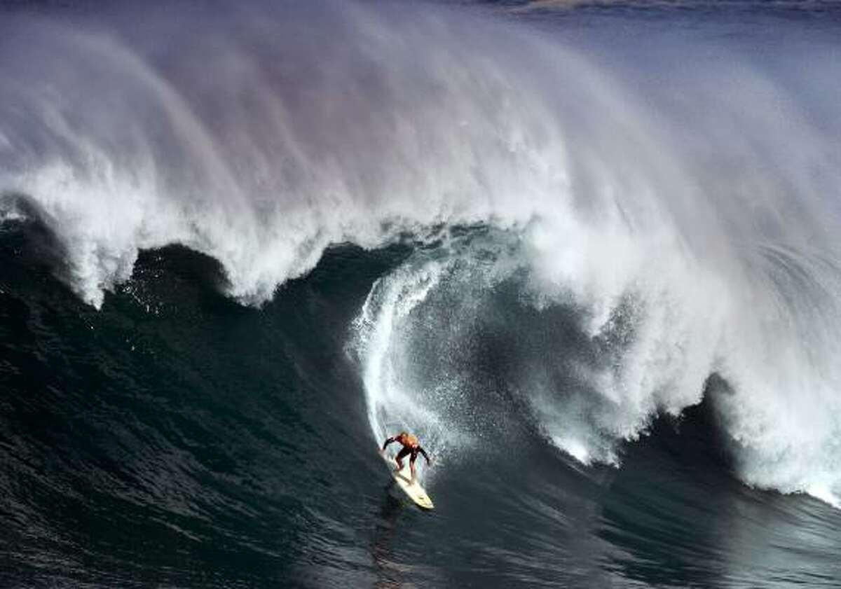 Kelly Slater surfs in a big wave surf contest on the North Shore at Waimea Bay, Hawaii.