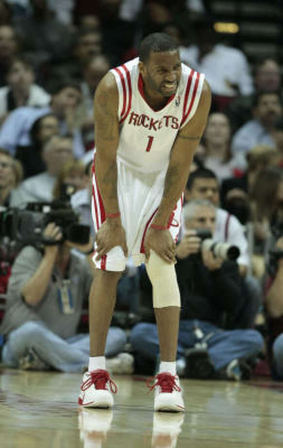 Tracy McGrady holds on to his knee and grimaces during Wednesday's loss to the 76ers. He left Friday's practice with a sprained left ankle. Photo: Billy Smith II |, Chronicle
