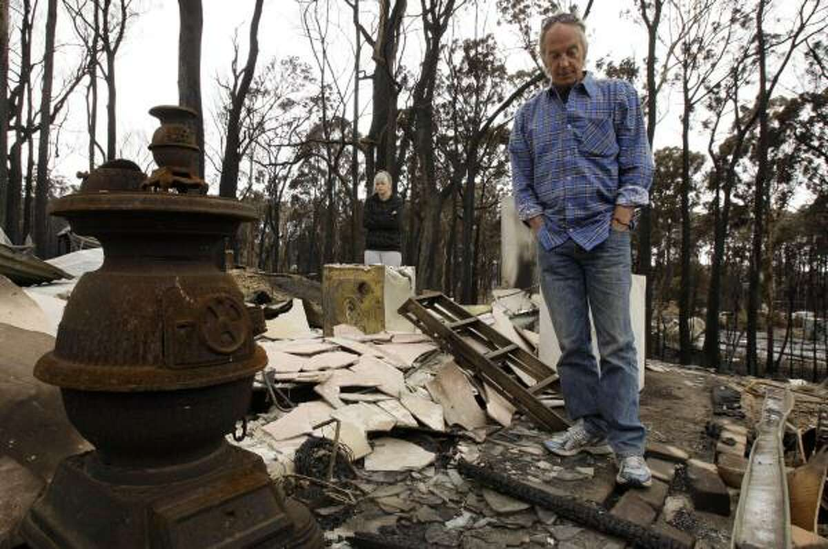 Peter Denson, right, and his daughter Amberley look through the wreckage of Peter's home at Kinglake, north east of Melbourne, Australia, on Feb. 11.
