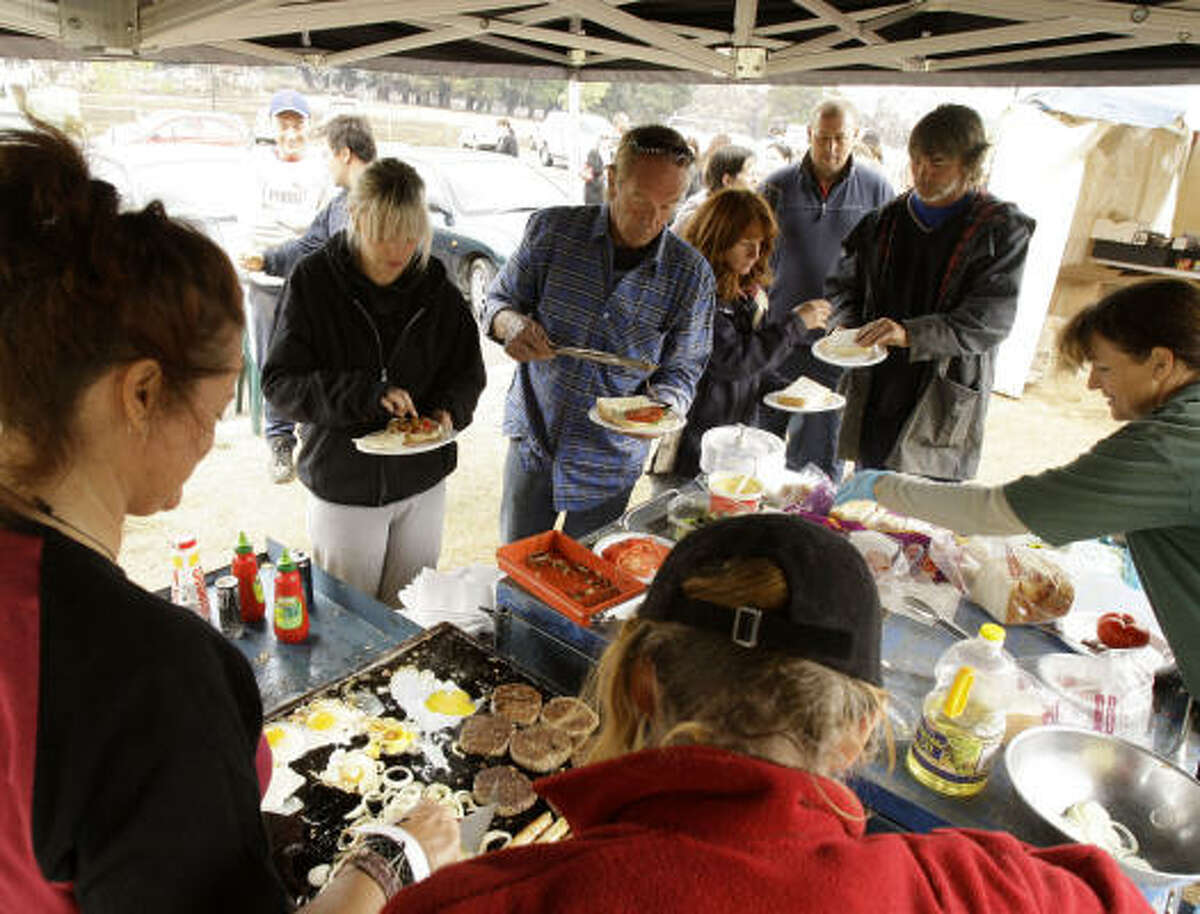 Peter Denson, center, and his daughter Amberley, second left, are given a donated lunch at the civic center at Kinglake, Australia, on Feb. 11.