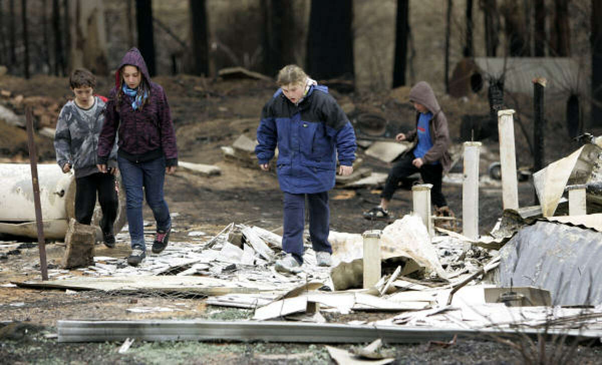 Twelve-year-old Rebecca Goudge, second right, and neighbors 9-year-olds Dean, left, and Kirk Mercuri, right, and their sister Alison, 11, walk around the wreckage of Goudge's home at Kinglake, northeast of Melbourne, Australia, on Feb. 11.