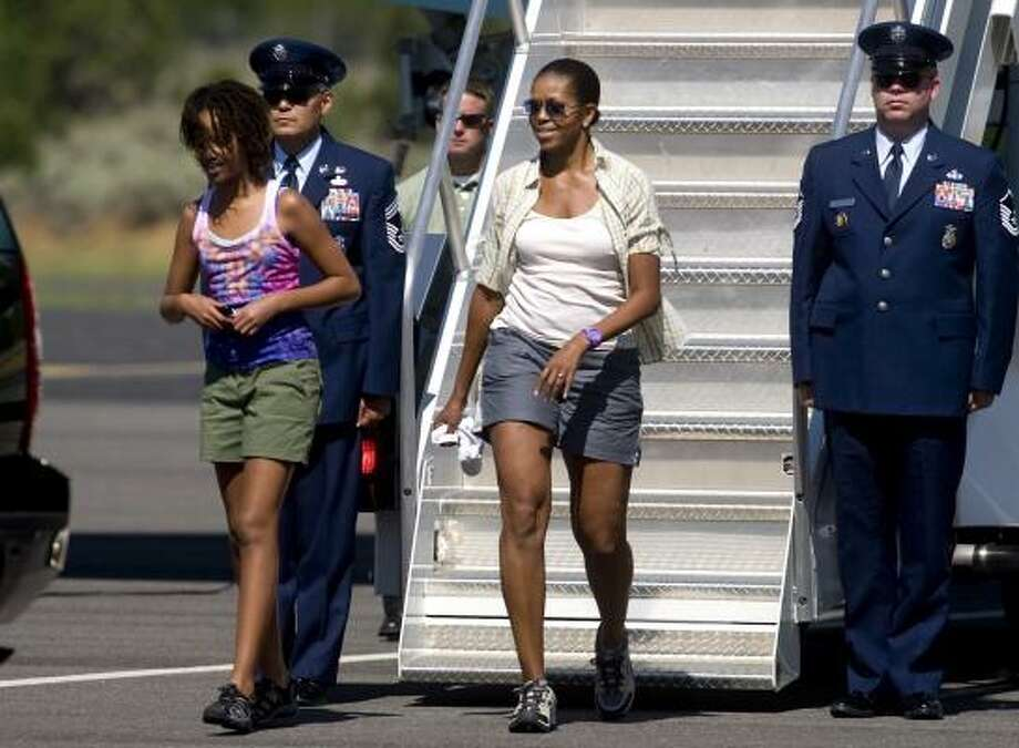 First lady Michelle Obama and daughter Malia walk off Air Force One at Grand Canyon National Park Airport in Tusayan, Ariz.,  Sunday. Photo: Dana Felthauser, AP
