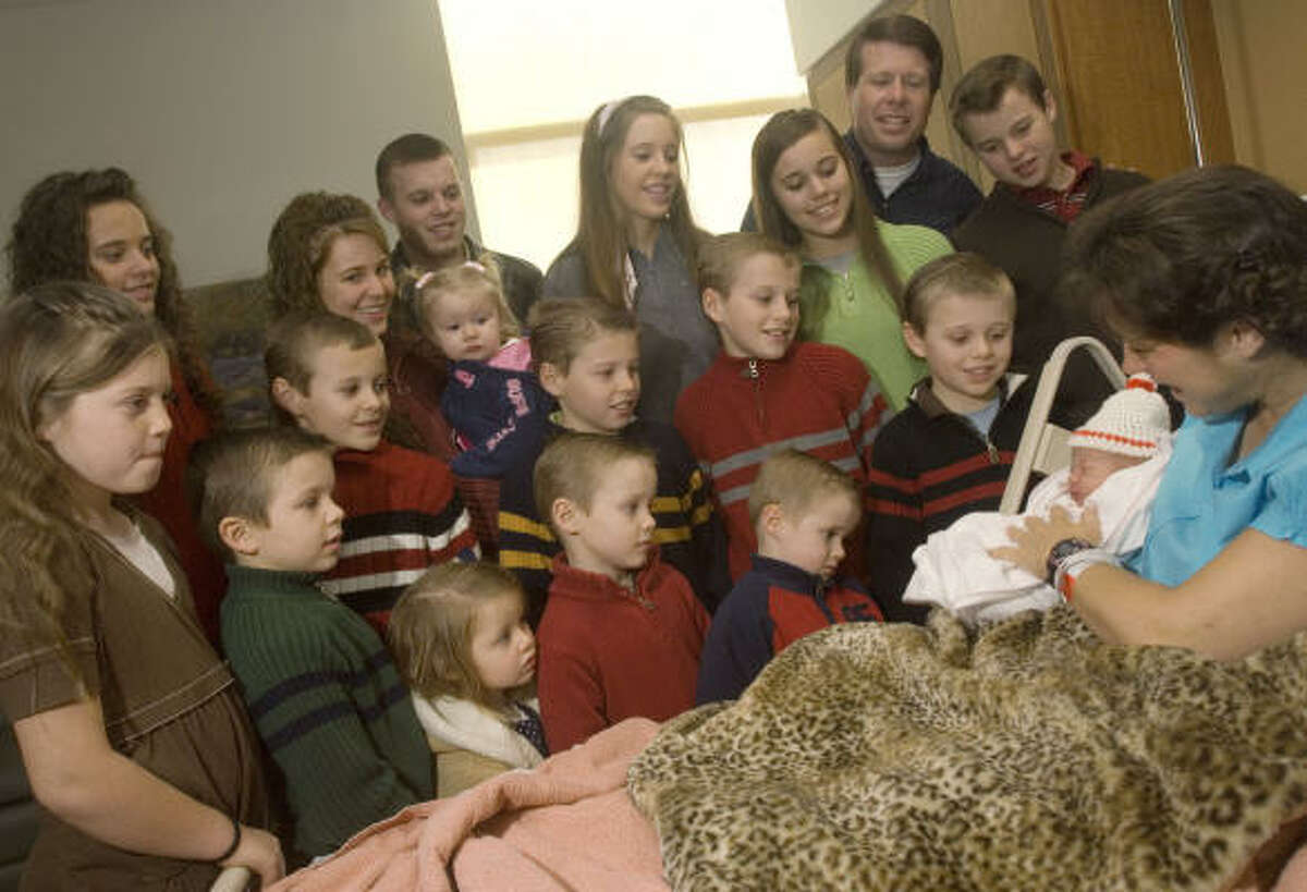 Michelle Duggar holds her newborn daughter, Jordyn-Grace Mikaya Duggar, as 16 of her other children and husband Jim Bob, second from the top right, look on.