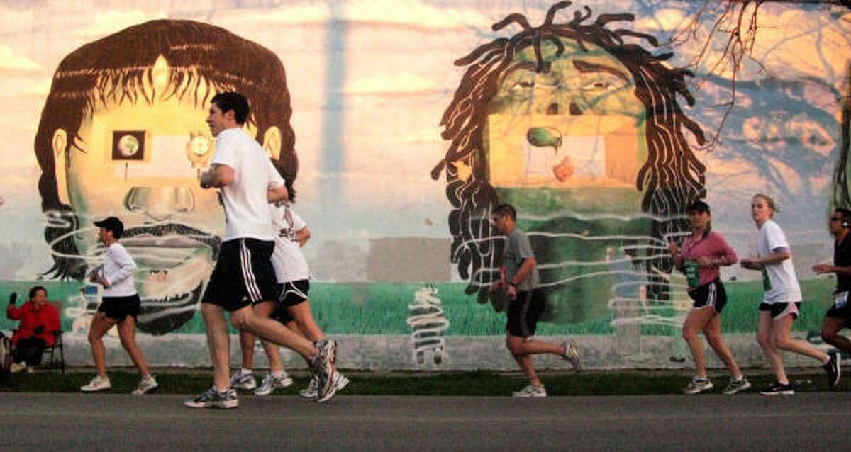 The marathon offered runners like Chronicle photographer Julio Cortez a fresh perspective on the city's diverse neighborhoods. Here, the field passes a mural on Quitman.