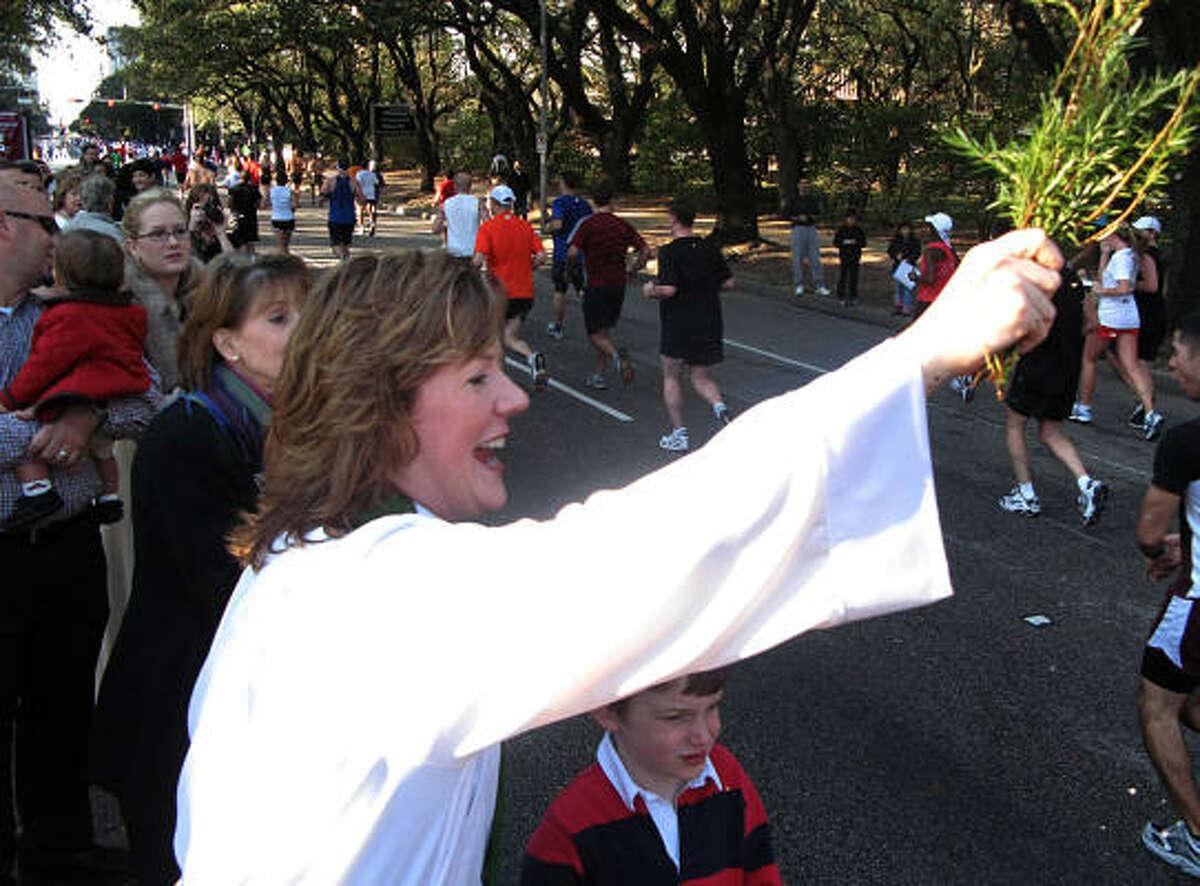 Genevieve Razim, associate director at Palmer Memorial Episcopal Church, offers marathoners some encouragement on Main Street near the Museum District.