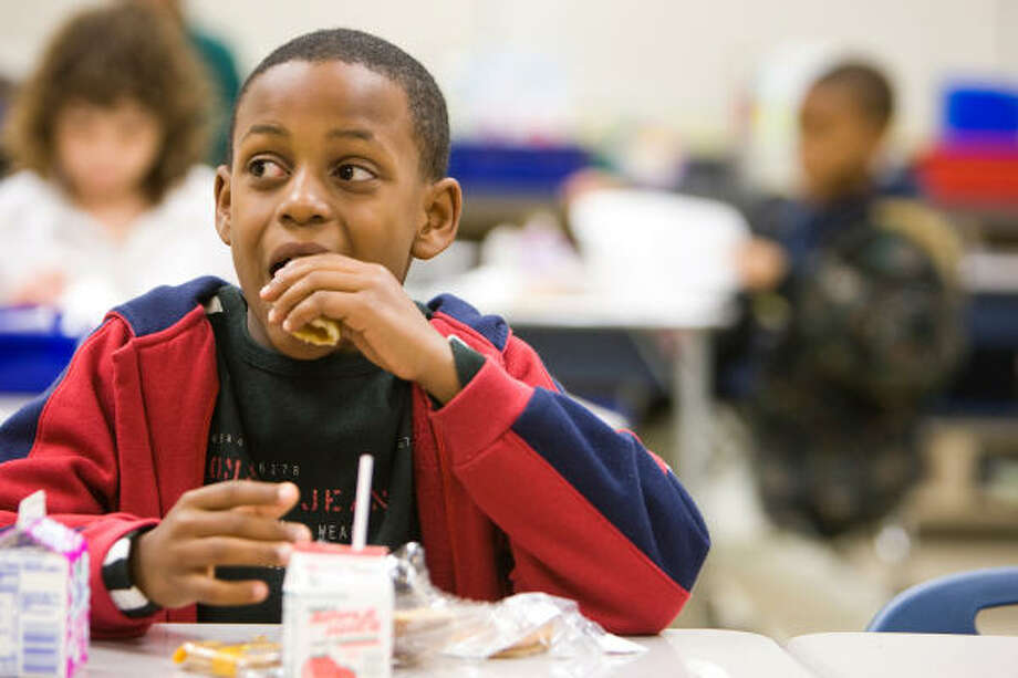 Kevin Canady, 9, a second-grader at HISD's Ruby Thompson Elementary, enjoys breakfast with his classmates on Friday. Photo: Nick De La Torre, Chronicle