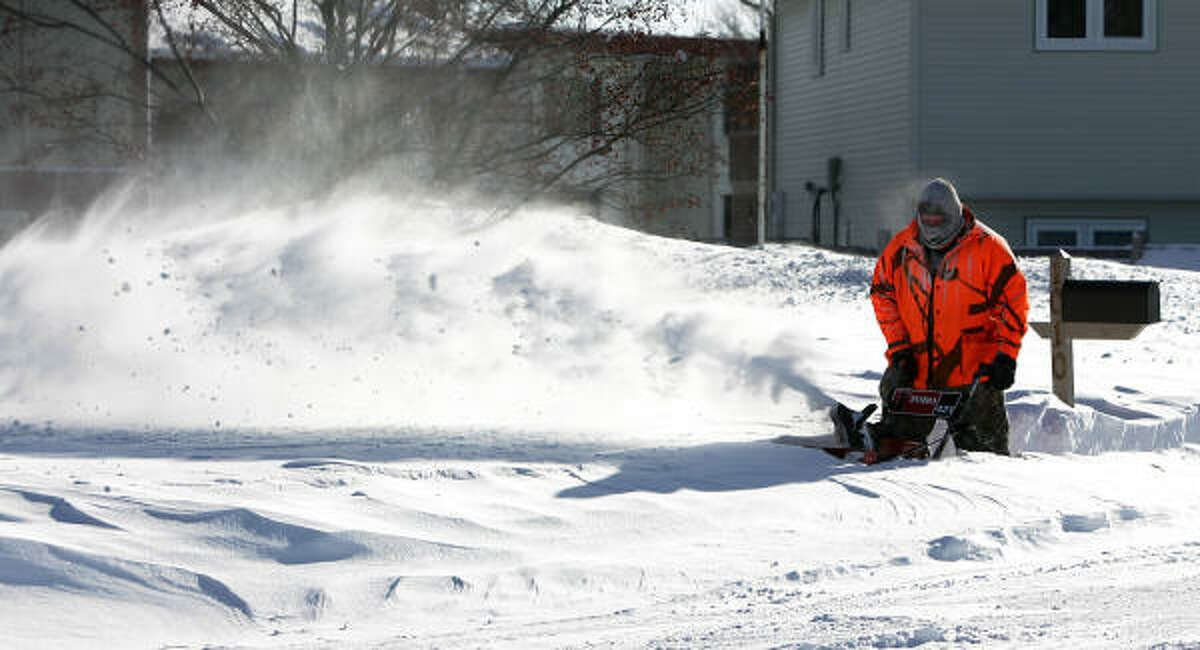 Dennis Mansavage uses a snow blower to help dig out Monday after another storm dumped more snow in Jamestown, N.D. More snow with falling temperatures are expected this week.