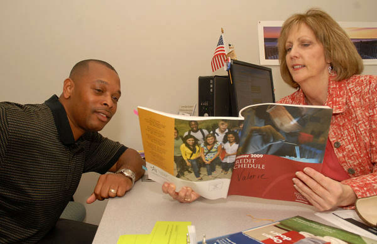 Lone Star College-Montgomery adviser Valerie Shepherd helps Tomball resident Rodney Baltrip, who recently lost his job and is taking courses at the college.