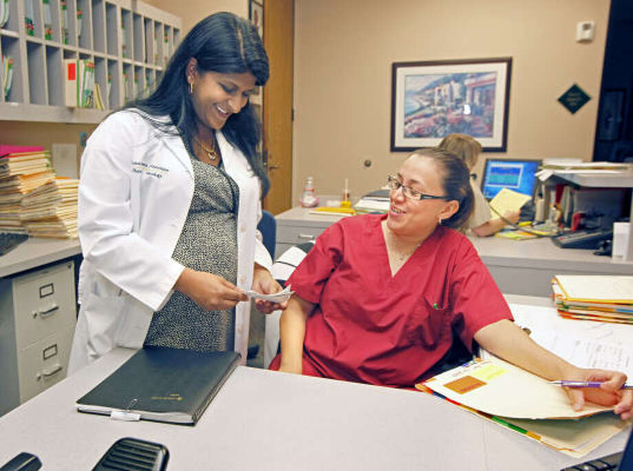 OB-GYN Rakhi Dimino shows colleague Alisa Gonzalez ultrasound images of Asha, the daughter Dimino is expecting on June 10. Photo: Craig Hartley, For The Chronicle
