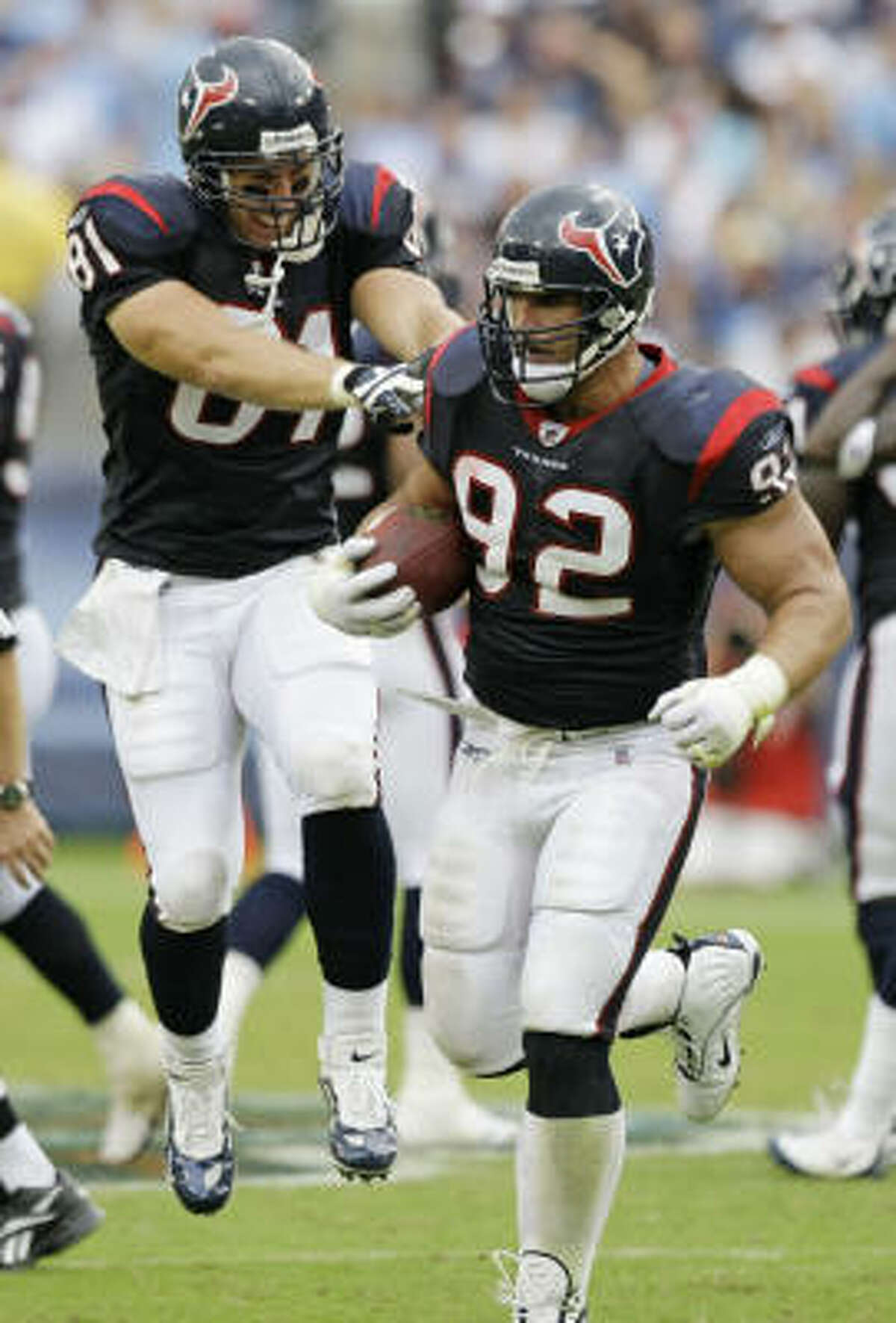 Texans defensive tackle Jeff Zgonina (92), at 39 the oldest player on the team, is congratulated by teammate Owen Daniels after Zgonina recovered a fumble by Kerry Collins late in the game.