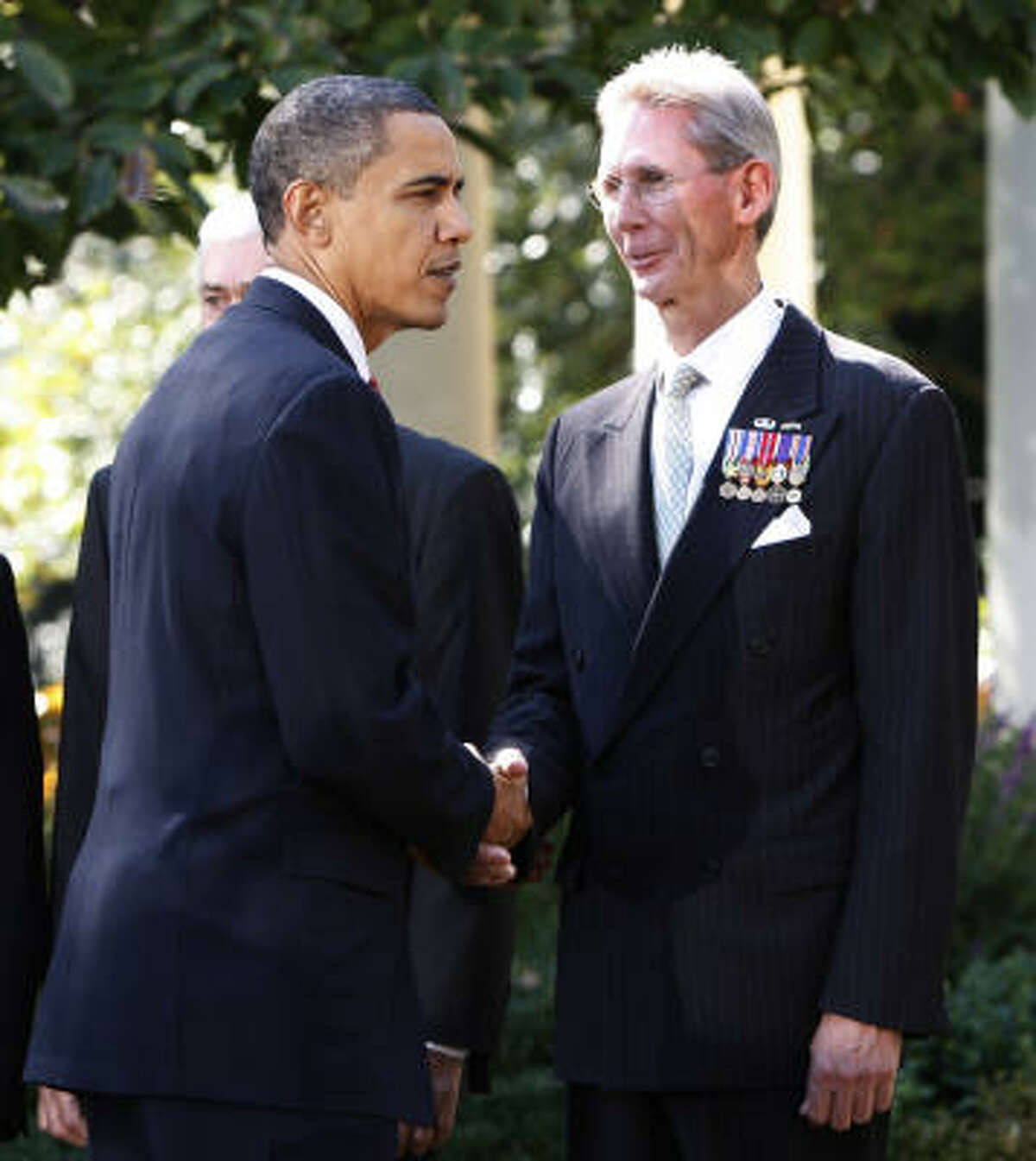 """President Barack Obama shakes hands with John Poindexter. """"We have an obligation to all who served in the jungles of Vietnam,"""" the president said."""