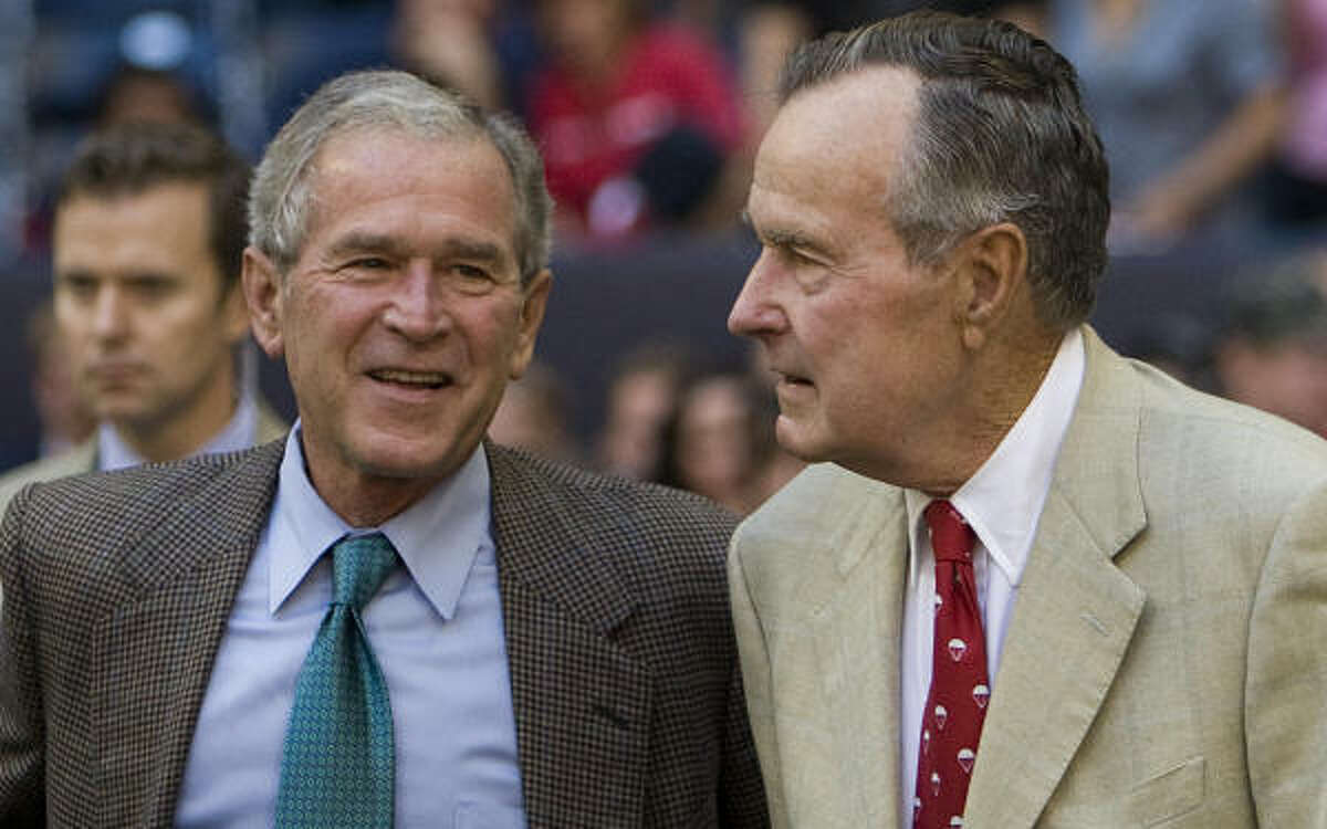 Former presidents George W. Bush, left, and George H.W. Bush watch from the sidelines before Sunday's game.