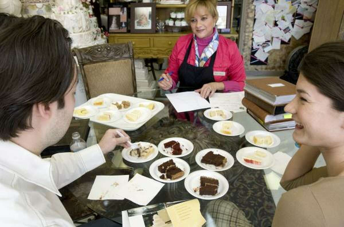 Jessie Lopez, center, helps Jared Gurley and Jennifer Procell, right, decide on a wedding cake at Edible Designs by Jessie on Thursday.