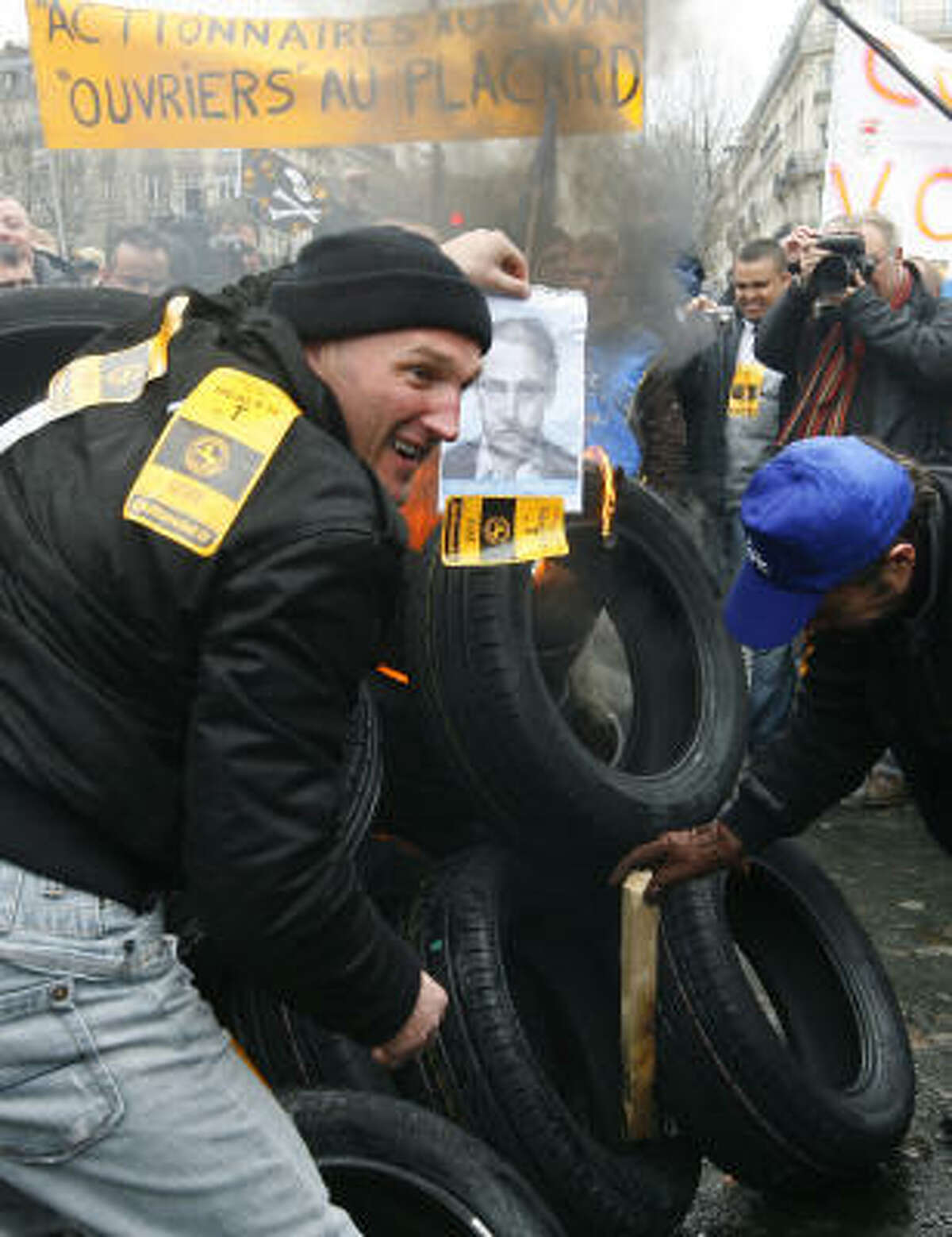 Continental employees of the Clairoix tire plant, northern France, burn tires and a photograph of plant director Louis Forzy during a demonstration Wednesday in Paris.