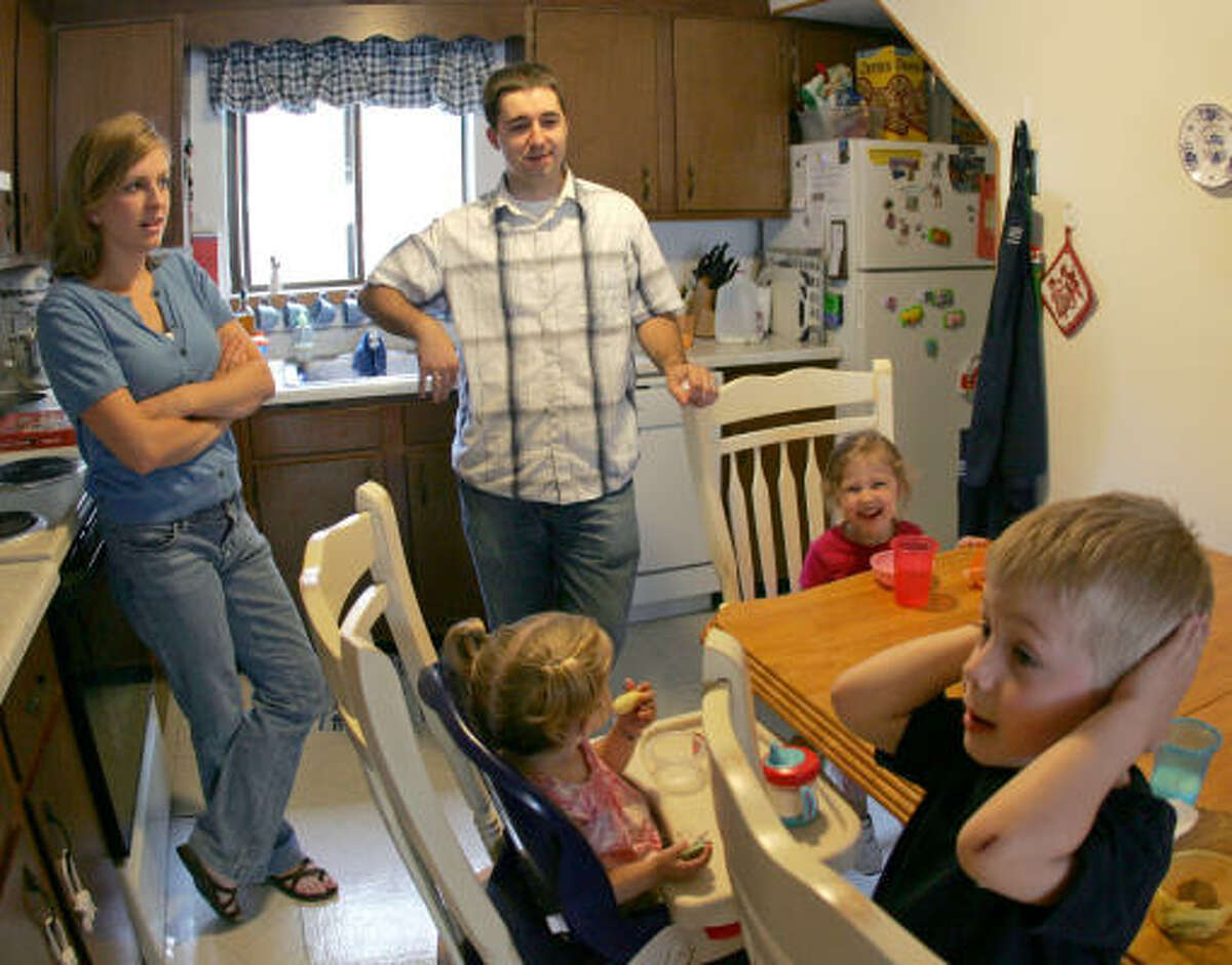 Mary and Chad Pugh, members of a baby-sitting co-op, supervise snack time with their children Jack, 3, right, and Marian, 1, center, and their friend Eva Evans, 3, in Watertown, Mass.