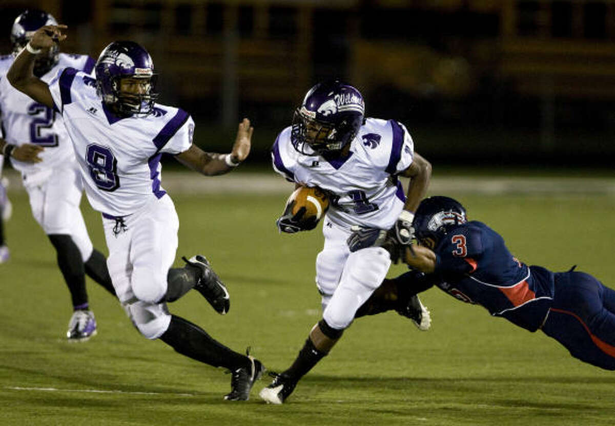 Angleton's Roderick Butler, center, breaks away from Dawson's Tre Olver, right, on this first-quarter run.