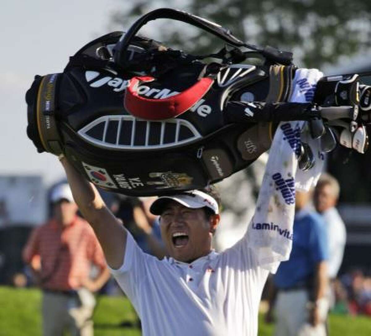 Y.E. Yang holds up his golf bag after winning the 91st PGA Championship at the Hazeltine National Golf Club.