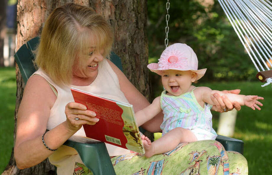 Margaret McManis reads one of the books she has written to her eight month old granddaughter Olivia Scank at McManis' home in River Plantation. Photo: David Hopper, For The Chronicle
