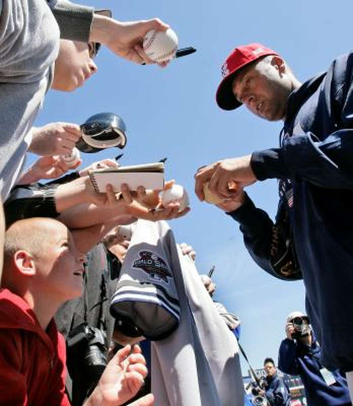 U.S. shortstop Derek Jeter, right, signs autographs before a spring baseball game against his club team, the New York Yankees.