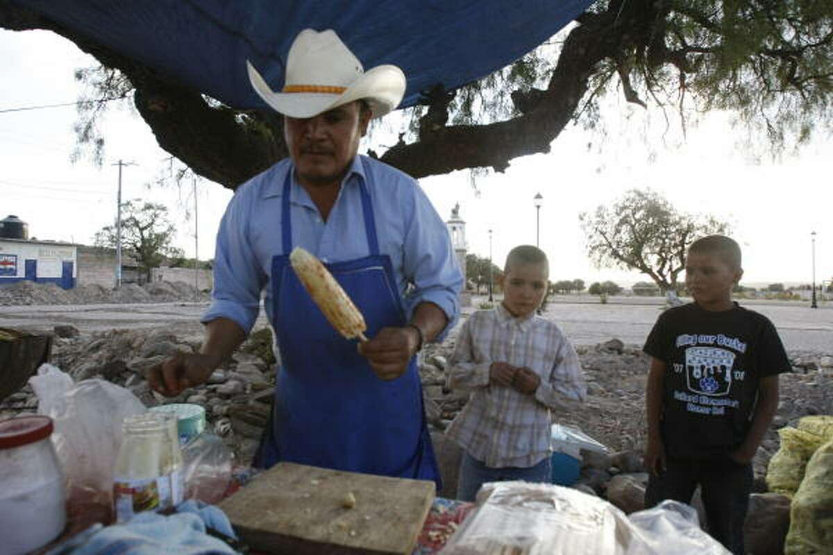 Jesus Ramírez (izq.), de 42 años y residente de Rancho Coral de Piedras, en el estado de Guanajuato, prepara un elote para la venta junto a sus hijos Juan Pablo (centro) y Cruz Abraham, de 8 y 9 años, cerca del pueblo de San Miguel de Allende.