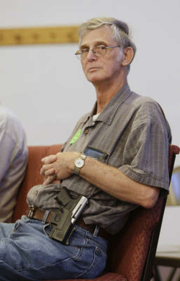 William Underwood attends service with his weapon on his hip. Photo: Ed Reinke, AP