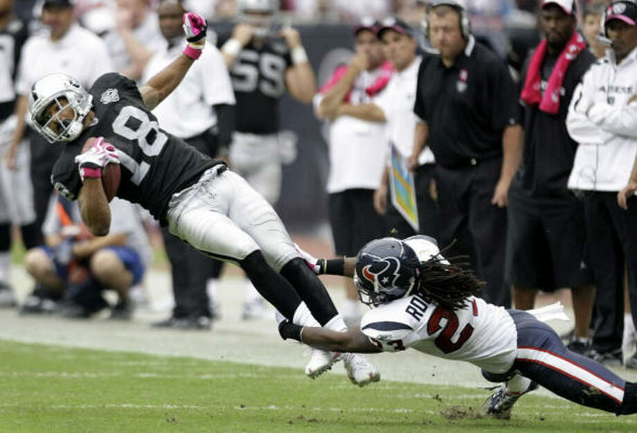 Sure tackling like this one by cornerback Dunta Robinson (23) on Raiders receiver Louis Murphy helped the Texans to their best defensive effort of the season. Photo: Brett Coomer, Chronicle