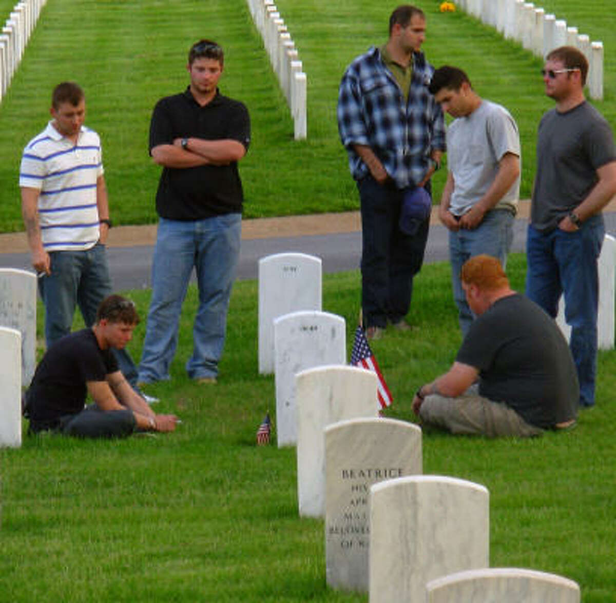 Jacob Blaylock, seated at left, one of four members in his unit to later commit suicide, joined other soldiers from his outfit at the St. Louis, Mo., grave of Brandon Wallace, who died in Iraq.